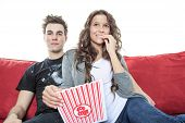 Close up portrait of young couple sitting together on a sofa at home watching television, joyfully s