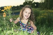 A little girl in sunset with flower