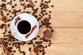 Cup Of Coffee, Chocolate, Sugar, Spices And Coffee Beans On A Wooden Background