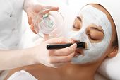 Cosmetic moisturizing mask is applied to the face of a woman.