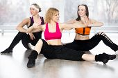 picture of zumba  - Sporty fitness instructor conducts aerobics training group of three smiling women doing dynamic sport exercises with choreographic elements in class - JPG