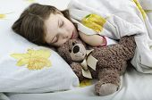 Little Girl Sleeping In Bed With Teddy Bear