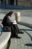 The nun studying at the edge of the fountain