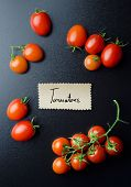 image of black-cherry  - Cherry tomatoes and handwritten note over black board above view - JPG