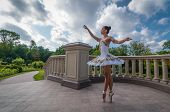 Ballerina Dancing Near Columns, Standing In Pointe Position. Outdoors, Spring