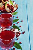 foto of pomegranate  - fresh pomegranate juice and ripe pomegranate seeds on a blue wooden background - JPG