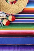 foto of traditional  - Mexican background with sombrero straw hat maracas and traditional serape blanket or rug - JPG