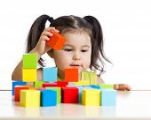 toddler girl builds a tower with colorful blocks