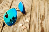 Blue Mirrored Sunglasses Wiht Reflection Of Martini Glass On The Wooden Background Close Up