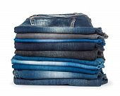 Stack Of Different Shades Of Blue Jeans On A White Background
