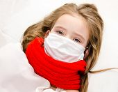 Sick Little Girl With Surgical Face Mask For Bacterial And Virus Flu Protection And Scarf