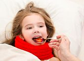 Sick Little Girl In Bed Taking Medicine