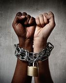 picture of chains  - white Caucasian hand chained with iron chain and locked together with black ethnicity female around wrists in togetherness multiracial respect and understanding concept - JPG