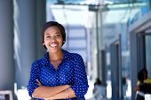 foto of buildings  - Portrait of a happy young business woman standing outside office building - JPG