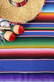 picture of mexican fiesta  - Mexican background with sombrero straw hat maracas and traditional serape blanket or rug - JPG