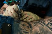 stock photo of modification  - Working hands of tattoo master - JPG