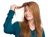 picture of split ends  - Young woman holding damaged long hair the hand and looking at split ends isolated on white background - JPG
