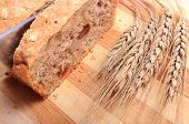 stock photo of fresh slice bread  - Knife slicing fresh baked wholemeal bread ears of wheat lying on cutting board - JPG