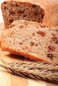 picture of fresh slice bread  - Slice of fresh baked wholemeal bread and ears of wheat lying on cutting board concept for healthy eating - JPG