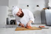 pic of chef knife  - Portrait of professional and experienced chef cook in uniform diligently cutting fish on fillets with knife on a board - JPG