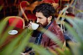 picture of coffee coffee plant  - Side view through plant leaves pensive fashionable hipster man holding cup of tea or coffee next to his mouth while sitting on the terrace of beautiful coffee shop - JPG