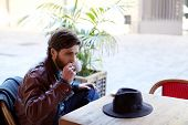 picture of coffee coffee plant  - Portrait of handsome fashionable hipster man holding cup of tea or coffee next to his mouth while sitting on the terrace of beautiful coffee shop - JPG