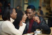 picture of san valentine  - Dark skinned woman feeding man with dessert cake at their dating - JPG
