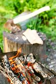stock photo of brazier  - firewood burning in outdoor brazier close up with ax in stump on background - JPG