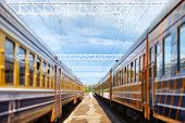 stock photo of passenger train  - Two passengers are along two passenger trains on one platform - JPG