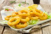 foto of deep  - deep fried calamari with lemon and salad on white tray - JPG