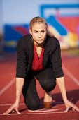 image of race track  - business woman in start position ready to run and sprint on athletics racing track - JPG
