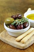 stock photo of kalamata olives  - black and green olives in oil with herbs - JPG