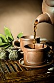stock photo of loam  - vertical photo of the clay teapot tea flow in cup on brown background tea ceremony - JPG