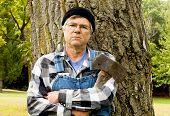 Mann, der eine Axt an einen Baum gelehnt hält