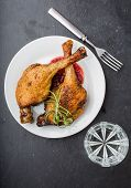 image of roast duck  - Roast duck legs with cranberries and fresh rosemary on white plate - JPG