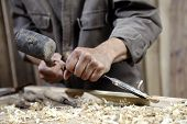 foto of chisel  - Hands Of Carpenter With A Hammer And Chisel On The Workbench In Carpentry - JPG