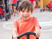 image of pedal  - happy boy child riding a pedal cart - JPG