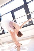 image of ballet barre  - Young Ballerina Wearing Pink Tutu Stretching in First Position at Barre in Sunny Dance Studio - JPG