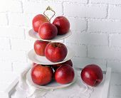 foto of serving tray  - Tasty ripe apples on serving tray on brick wall background - JPG