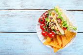 picture of tacos  - Tasty taco with nachos chips and vegetables on plate on table close up - JPG