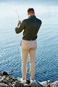 picture of street-rod  - Man casting with light rod on the river against the water surface - JPG