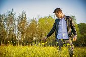 stock photo of grassland  - Handsome young man at countryside - JPG