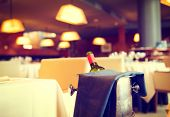 Постер, плакат: Served dinner table in a restaurant Restaurant interior Cozy restaurant table setting Defocused b