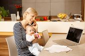 stock photo of young baby  - Young mother working from home - JPG