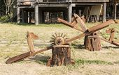 picture of seesaw  - Empty wooden seesaw in garden with old houses in the countryside - JPG