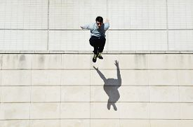 stock photo of parkour  - Male parkour free runner jumping forward from high rooftop over cement building background young tracer athlete jumping over building roof at sunny day - JPG