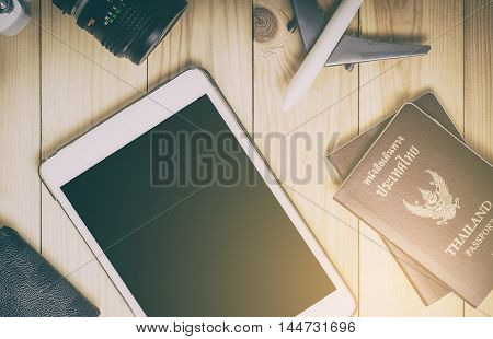 poster of Blank tablet screen with travel equipments. Travel items and tablet on wooden table in vintage tone. Blank tablet screen for travel advertisement, travel website and travel agencies service.