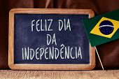the text Feliz Dia da Independencia, Happy Independence Day written in Portuguese in a chalkboard, a poster