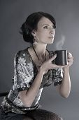 Attractive lady with a cup of coffee over grey background