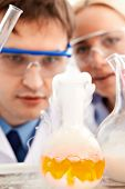 Serious clinicians looking at flask with steaming yellow liquid in laboratory poster